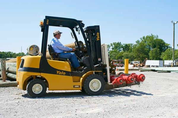 A man driving a yellow and black Yale forklift while also handling some loose heavy equipment.