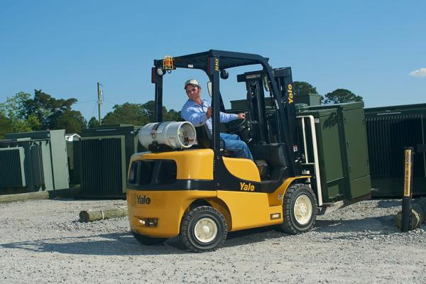 A man operating a yellow and black Yale forklift while handling pieces of heavy metal material.