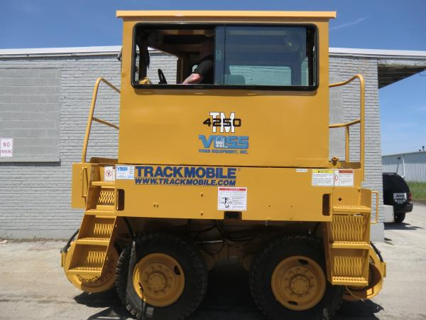 A man sitting inside of a yellow Voss Equipment piece of heavy machinery that is stationed outside of a warehouse.
