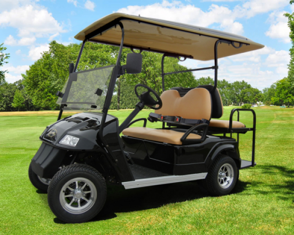 A black Star electric vehicle is parked on a green golf course track.