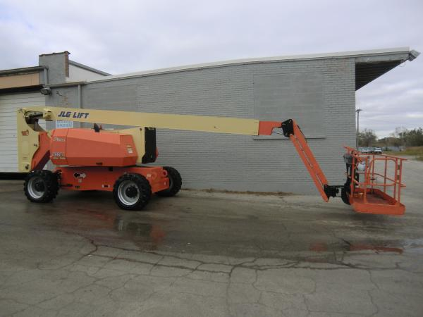 A JLG Lift crane is stationed outside of grey brick building in the parking lot.