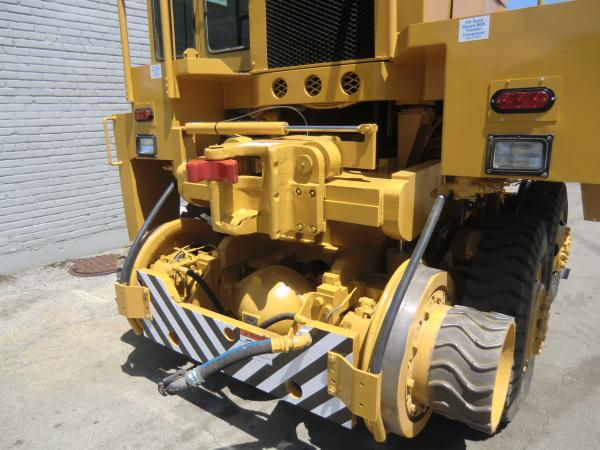 A large piece of yellow heavy machinery with a roller attachment connected to it that is parked outside of a warehouse.