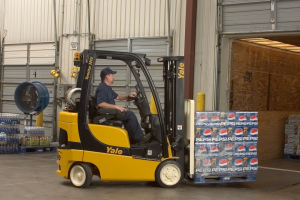 A man operating a black and yellow forklift while handling cases of Pepsi-Cola inside a warehouse.