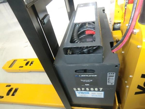 A close-up shot of the electric generator of a black and yellow Yale pallet jack.