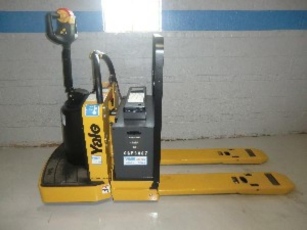 A stationary black and yellow Yale pallet jack sits in front of a grey warehouse wall with blue trimming.