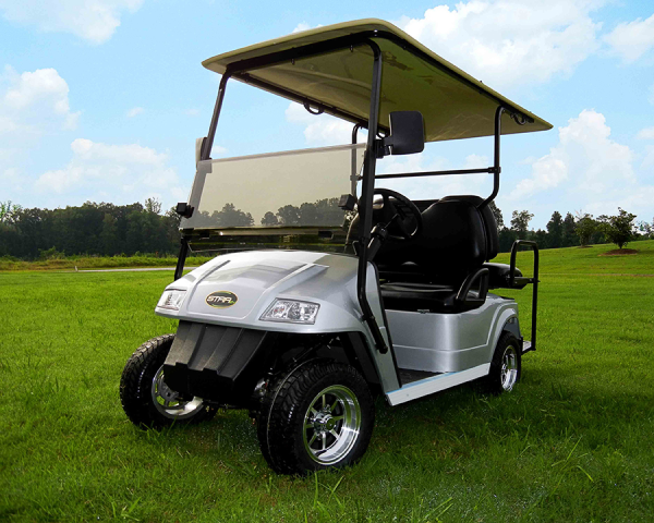 A silver Star electric vehicle that is parked on a piece of green golf pasture.