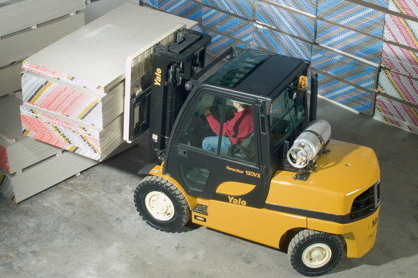 A man is operating a yellow and black forklift to move various material.