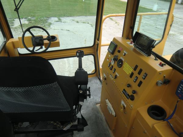 The inside cab of a large piece of heavy machinery that includes an operating board and steering wheel.