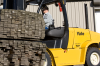 A black and yellow Yale forklift is being operated by a man who is transporting two large piles of wood.