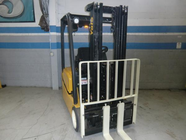 A yellow and black Yale forklift that is parked in front of a grey warehouse wall with blue trimmed stripes.