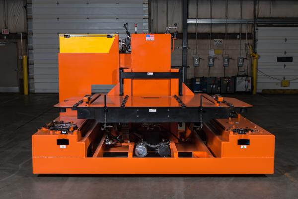A large orange piece of heavy machinery sits in an empty warehouse.
