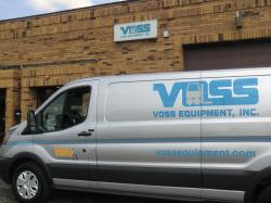 A silver van is parked next to a brick building with the material handling brand, Voss Equipment's image on the van.