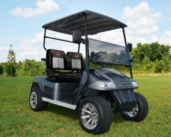 A black Star electric vehicle that is parked outside on the grass of a golf course.