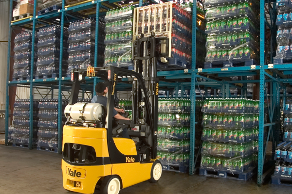 A man is operating a black and yellow Yale forklift to retrieve soda's off of warehouse shelving.