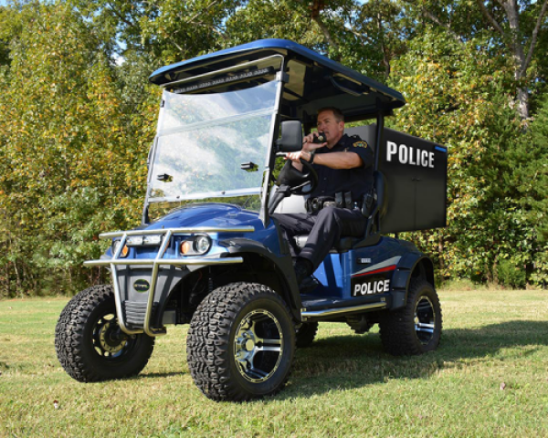 A blue and black electric police cart is parked on a patch of grass in front of a tree line while an officer sits inside of it.