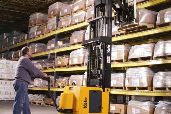 A man operating a black and yellow forklift in a warehouse.