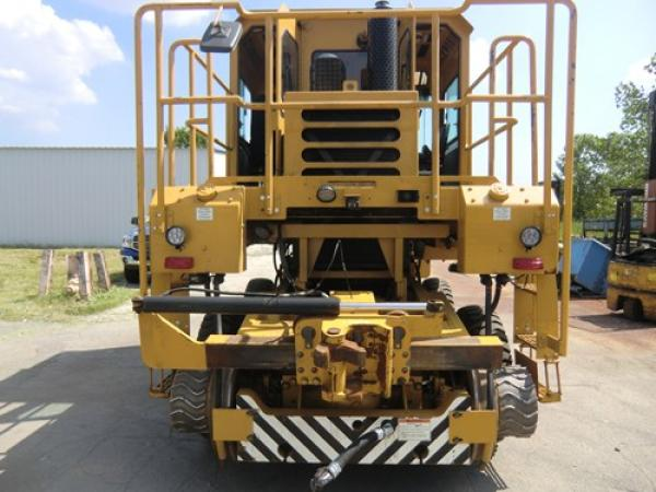 A large piece of yellow heavy machinery is located outside in a road by a warehouse.