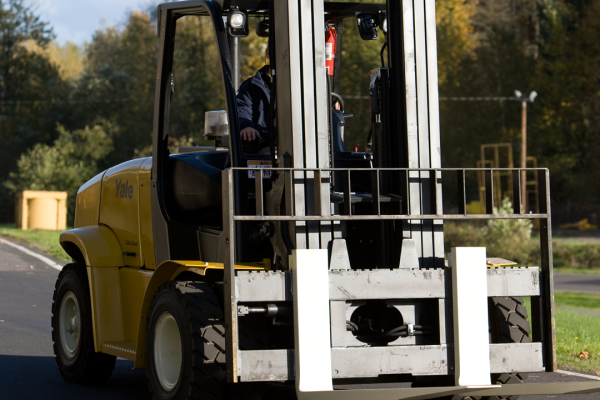 A black and yellow Yale forklift that is outside.