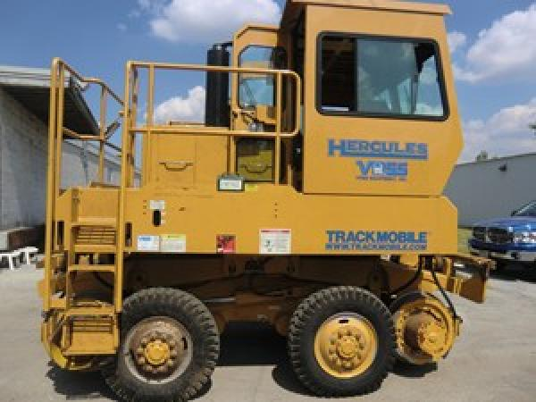A large yellow Hercules piece of heavy machinery is stationed outside of a warehouse in a parking lot.