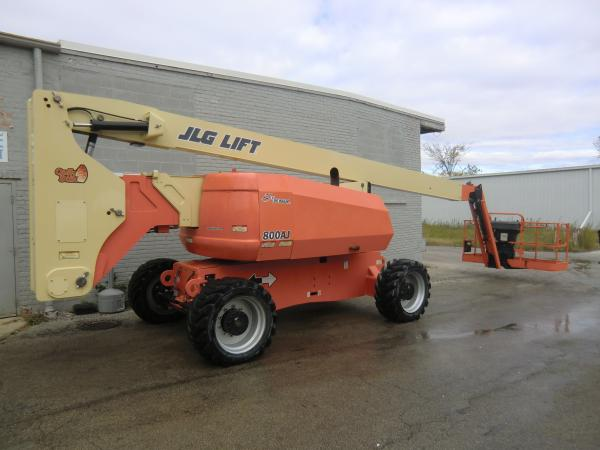 A stationary JLG Lift that is parked outside of a grey brick building.