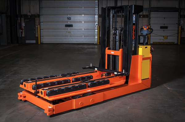 An orange piece of heavy machinery that is located inside of a warehouse.