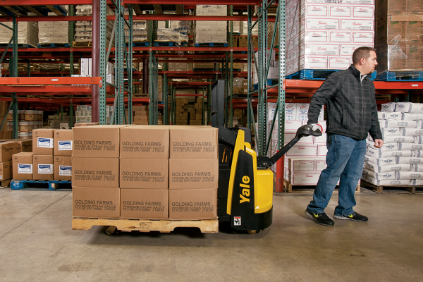 A man operating a yellow and black Yale pallet jack while transporting boxes on a wooden pallet.