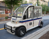 A Star electric vehicle that is designed to be a police vehicle sits outside parked on a road.