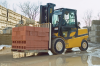 A man is operating a yellow and black Yale forklift outside while moving brick cinderblocks.