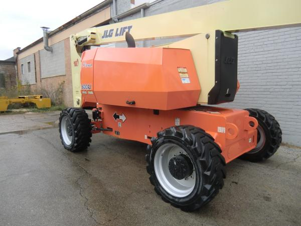 A orange JLG lift is parked outside of a grey brick building in a parking lot.