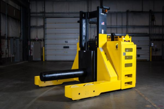 A large piece of material handling equipment that is stationed in an empty warehouse.