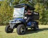 A blue and black electric police cart is parked on a patch of grass in front of a tree line with an officer inside of it.