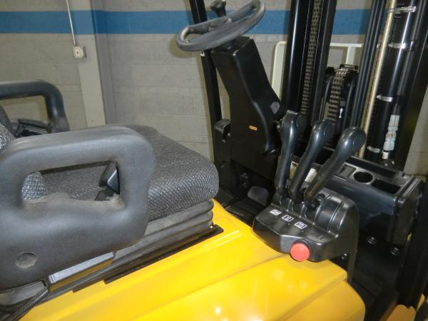 A close-up shot of the seat and operating area of a black and yellow Yale forklift.