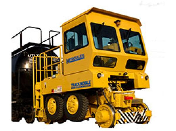 A large yellow Hercules railroad shunter is stationed in front of a white backdrop.