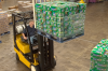 A man is operating a black and yellow Yale forklift to move Sierra Mist packages across the warehouse.