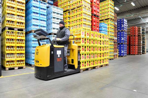 A man operating a black and yellow Yale forklift in a warehouse to move material.