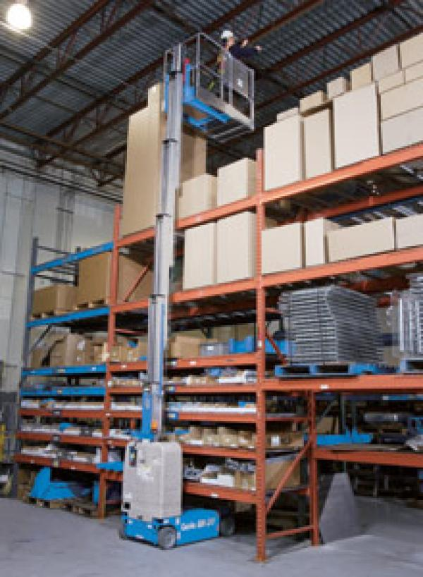 A person working in a warehouse while fully extended in the air by a blue crane lift.
