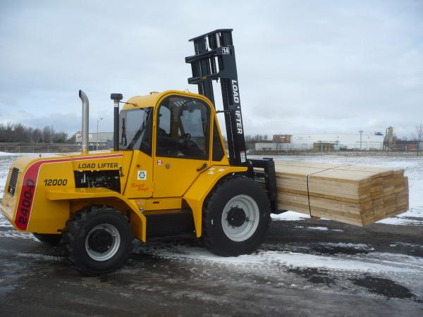 A black and yellow forklift is outside in the snow while handling a pile of wood