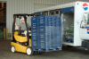 A man in a black and yellow Yale forklift moving a large shipment of Pepsi Cola boxes.