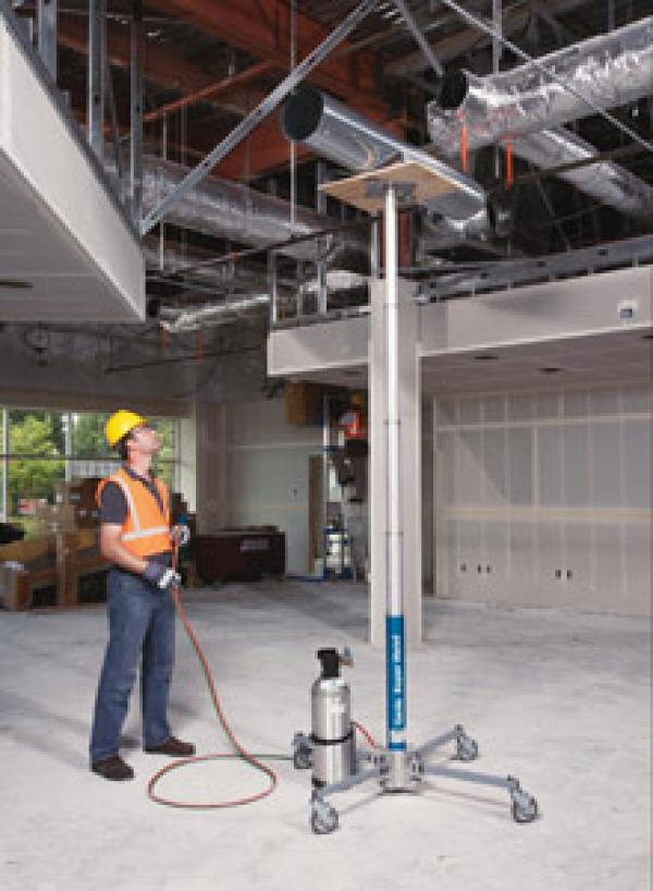 A man in a yellow hard hat and orange safety vest is operating a hydraulic jack lift to lift ventilation to the ceiling.