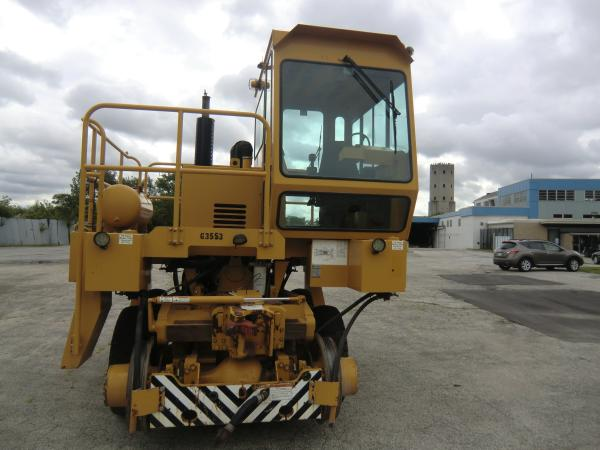 A large piece of yellow heavy machinery that is stationed outside in a parking lot for machines.