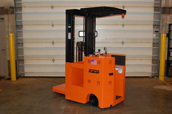 An orange Rico forklift that is stationed inside of a warehouse.