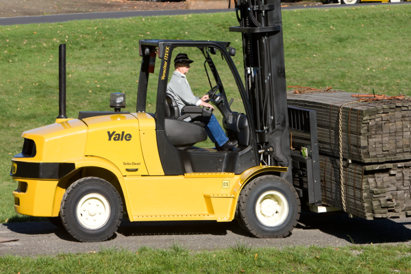 An operator driving a yellow and black forklift that is about to handle some material on wooden pallets.