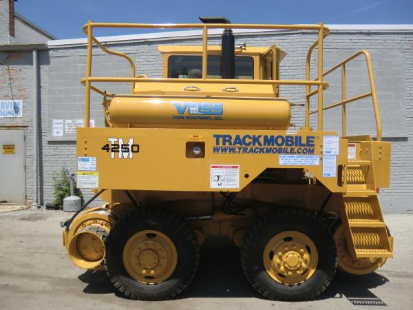 A piece of yellow Voss heavy equipment that is parked outside in front of a warehouse.