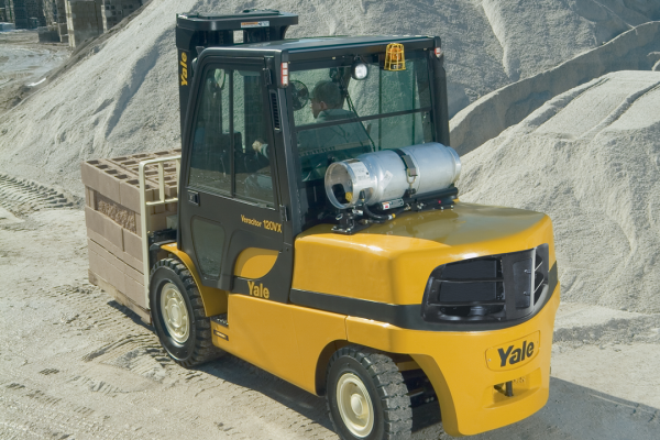 A yellow and black Yale forklift is lifting stone cinderblocks while outside.