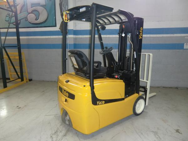 A stationary black and yellow Yale forklift sits in front of a grey warehouse wall with blue trimming.